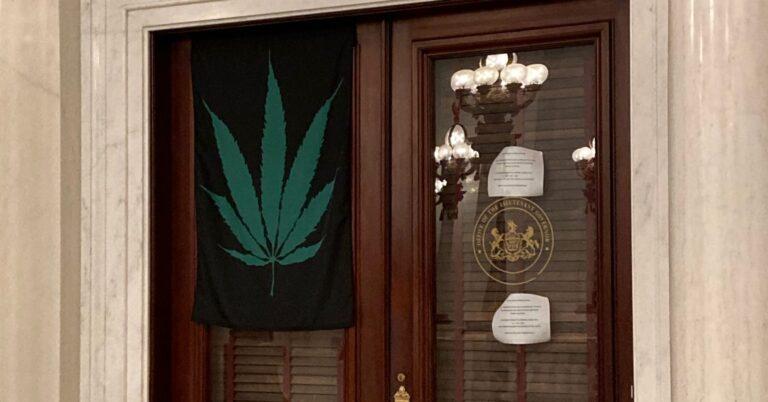 A marijuana leaf flag hangs on the door of Lt. Gov. John Fetterman's office on Sept. 21, 2020. (Sam Dunklau / WITF)
