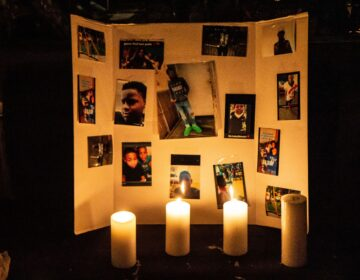 Photos of 12 year-old Sadeek Clark-Harrison and candles honor his life on his porch in Frankford. (Kimberly Paynter/WHYY)