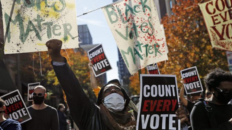 Zhanon Morales, 30, of Philadelphia, raises her fist during a Nov. 5 voting rights rally in Philadelphia. Rebecca Blackwell/AP