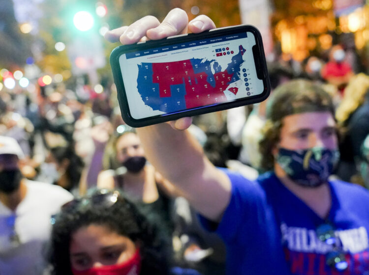 A supporter of President-elect Joe Biden holds up his mobile phone to display the electoral college map outside the Philadelphia Convention Center