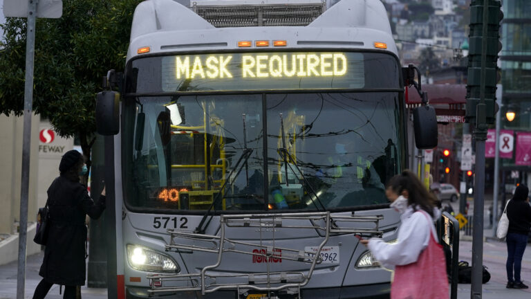 A sign on a San Francisco bus advises that passengers are required to wear masks. Health officials have renewed pleas for Americans to protect themselves and others from the coronavirus as the death toll passes 250,000. (Jeff Chiu/AP)