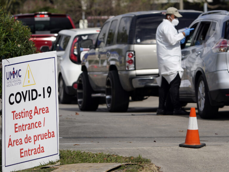 A healthcare worker processes people in line at a United Memorial Medical Center COVID-19 testing site on Nov. 19, in Houston. Texas is rushing thousands of additional medical staff to overworked hospitals as the number of hospitalized COVID-19 patients increases. (David J. Phillip/AP)