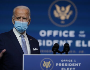 Joe Biden stands at a podium wearing a face mask
