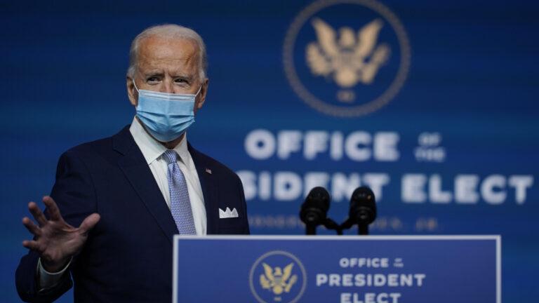 Joe Biden stands at a podium wearing a face mask