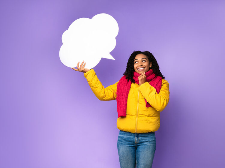 A cheerful Black woman holding an empty speech bubble above her head