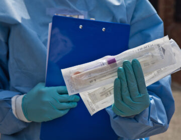 Dr. Ala Stanford, a pediatric surgeon, holds COVID-19 testing materials outside the mobile testing site of the Black Doctors COVID-19 Consortium. (Kimberly Paynter/WHYY)