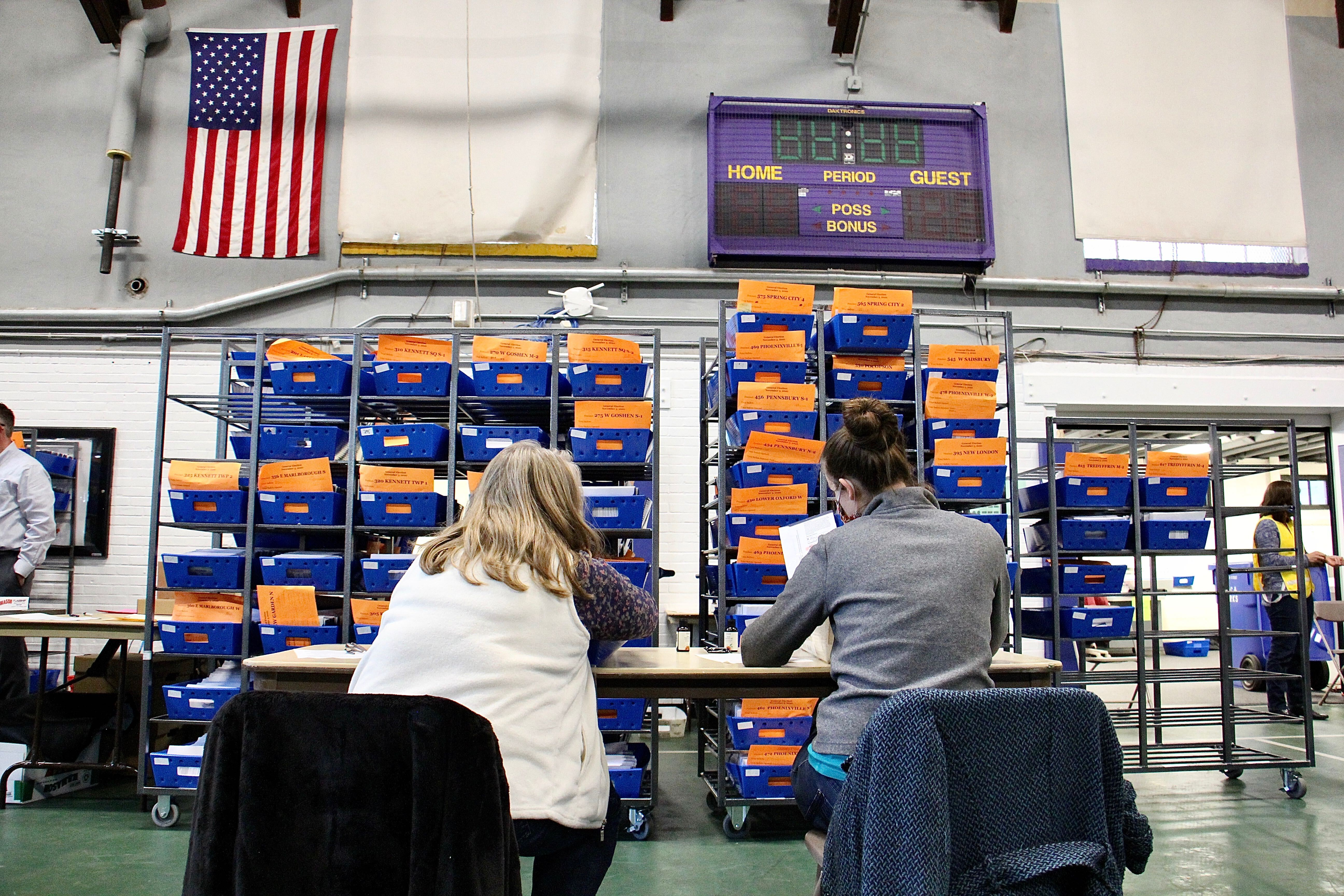 Chester Country election workers check ballots one last time before sending them to be scanned and counted in the West Chester University gym.