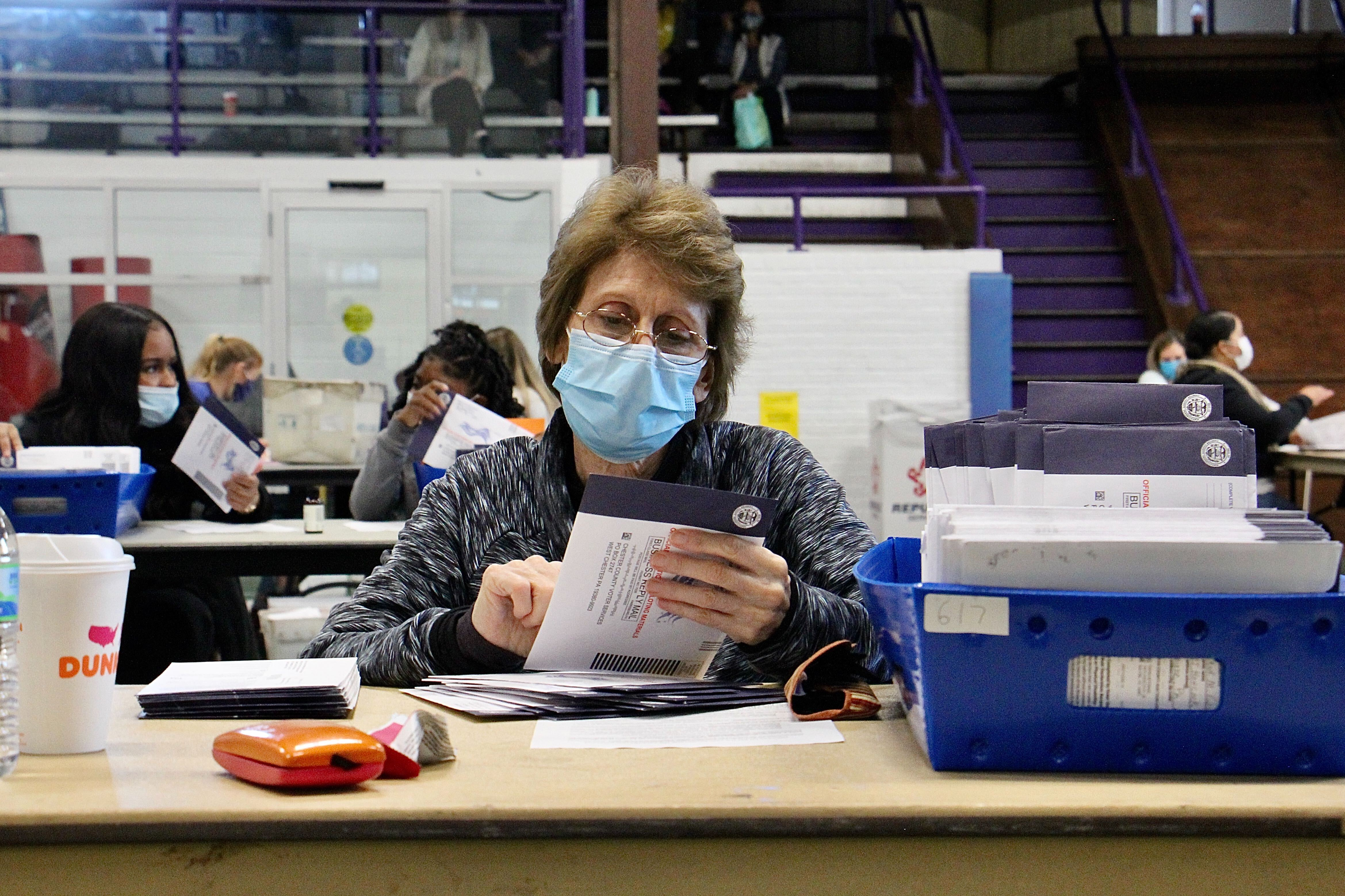Election worker Patricia Masi inspects mail-in ballots at the West Chester University gym