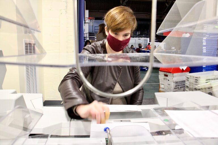 Margaret Hodgkiss-Lilly operates an extractor, which removes ballots from their envelopes