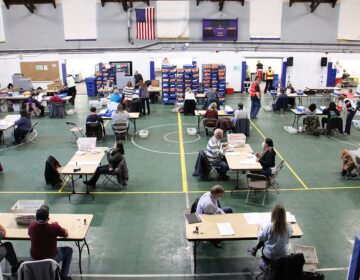 Chester County election workers sort, inspect, flatten and scan mail in ballots at the West Chester University gym.