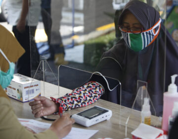 Health workers measure a woman's blood pressure during a simulation of a COVID-19 vaccine trial in Indonesia. (Adriana Adie/NurPhoto via Getty Images)