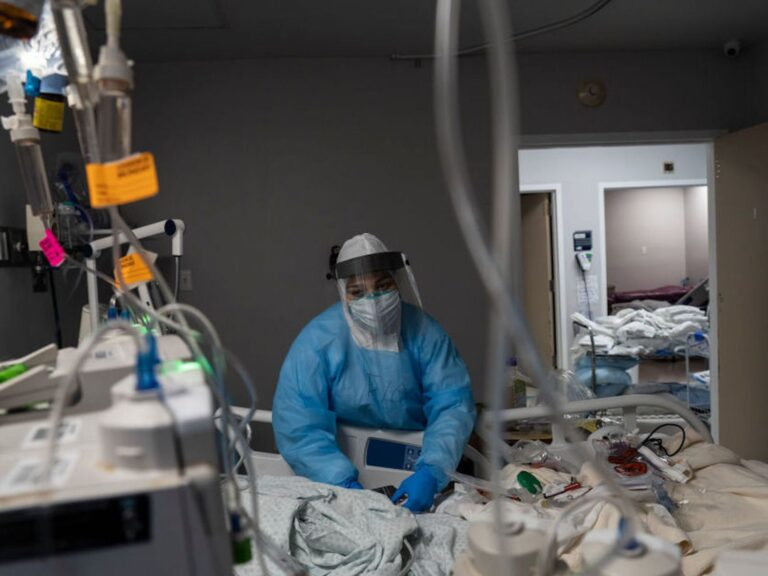 A health care worker treats a COVID-19 patient at the ICU at United Memorial Medical Center in Houston, Texas.
