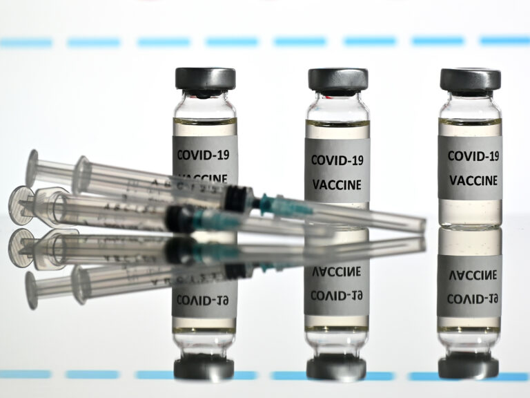 An illustration picture shows vials with COVID-19 vaccine stickers attached and syringes with the logo of U.S. biotechnology company Moderna on November 17.