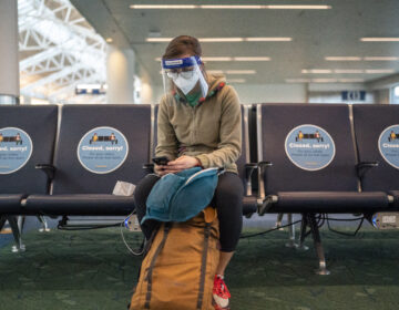A traveler waits for a flight at Portland International Airport in Oregon last week. Public health experts say it's important that people who traveled or gathered with others are especially careful over the next two weeks. (Nathan Howard/Getty Images)