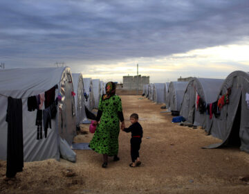 A Kurdish refugee mother and son from the Syrian town of Kobani walk beside their tent in a camp in the southeastern town of Suruc on the Turkish-Syrian border in 2014 in Sanliurfa, Turkey. President-elect Joe Biden aims to reverse the Trump administration's dramatic cuts to refugee admissions. (Gokhan Sahin/Getty Images)