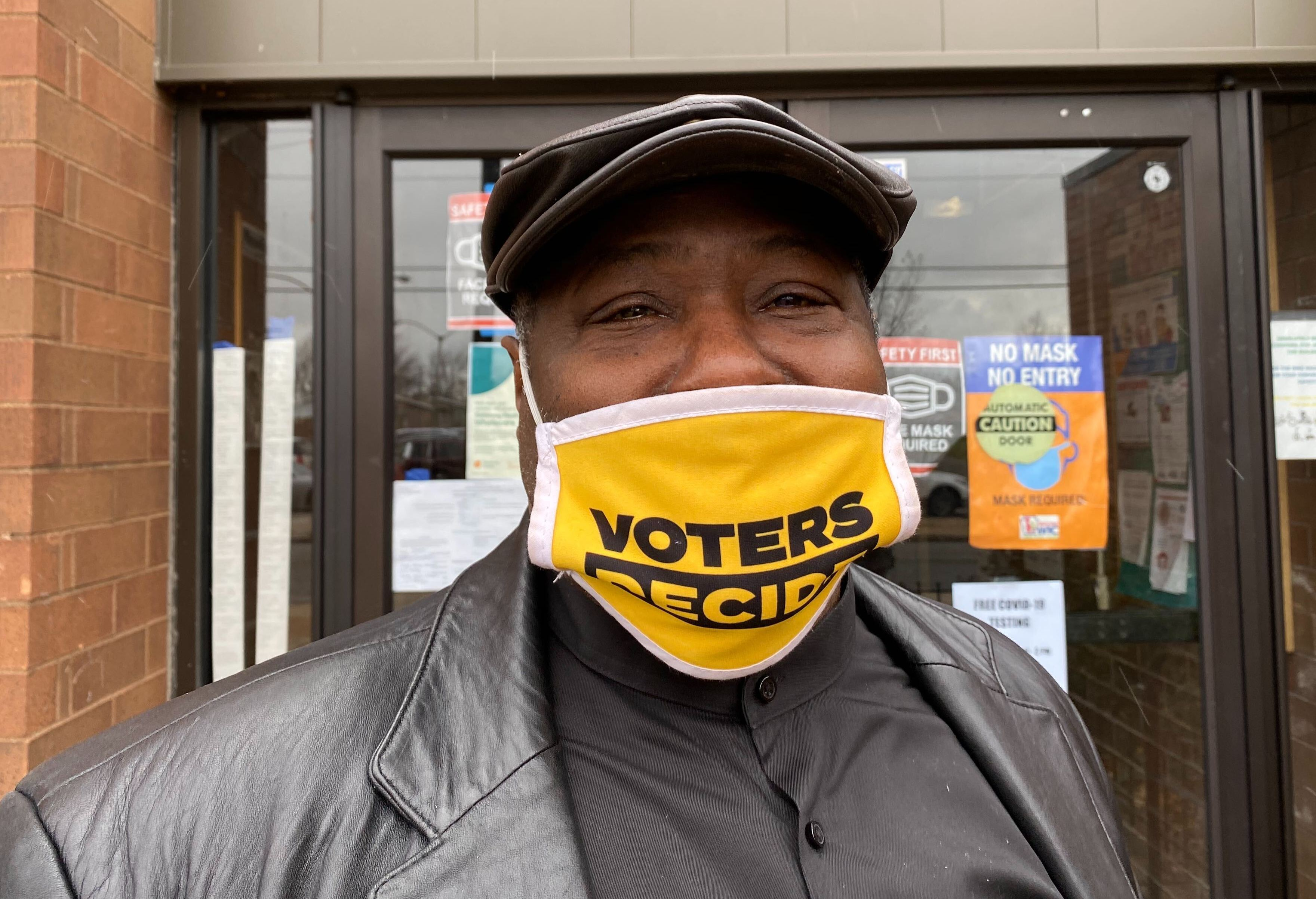 """Michael Keys wears a mask that says """"VOTERS DECIDE"""""""