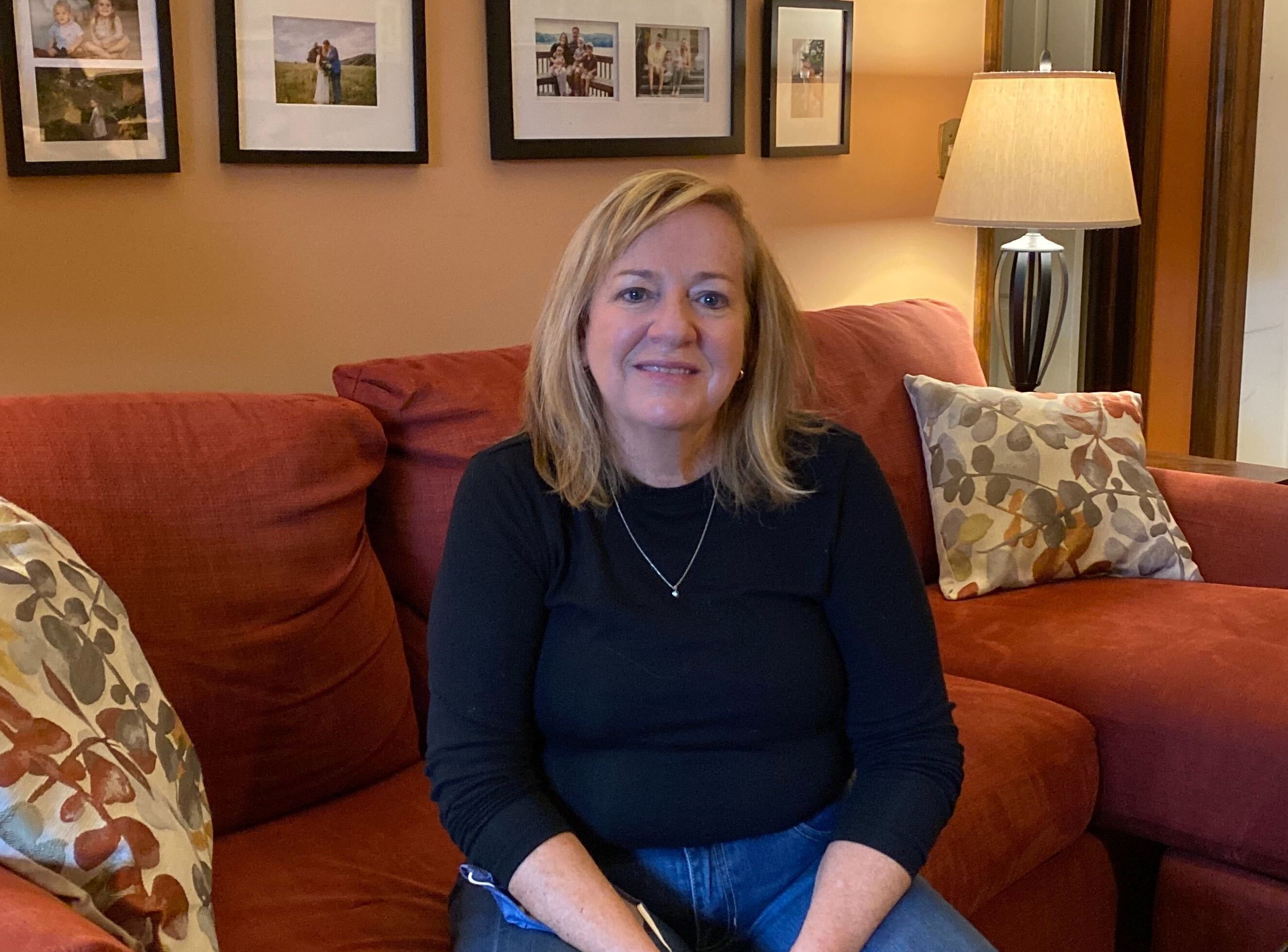 Maryann Frontino sits on a couch