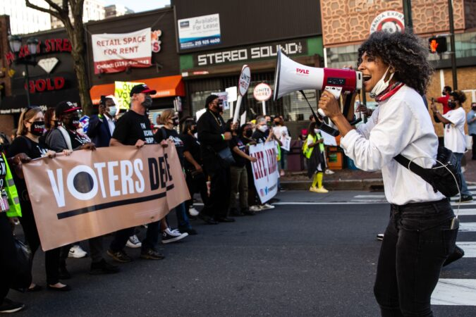 Sam Pride of Girls Rock Philly leads a song as demonstrators celebrate