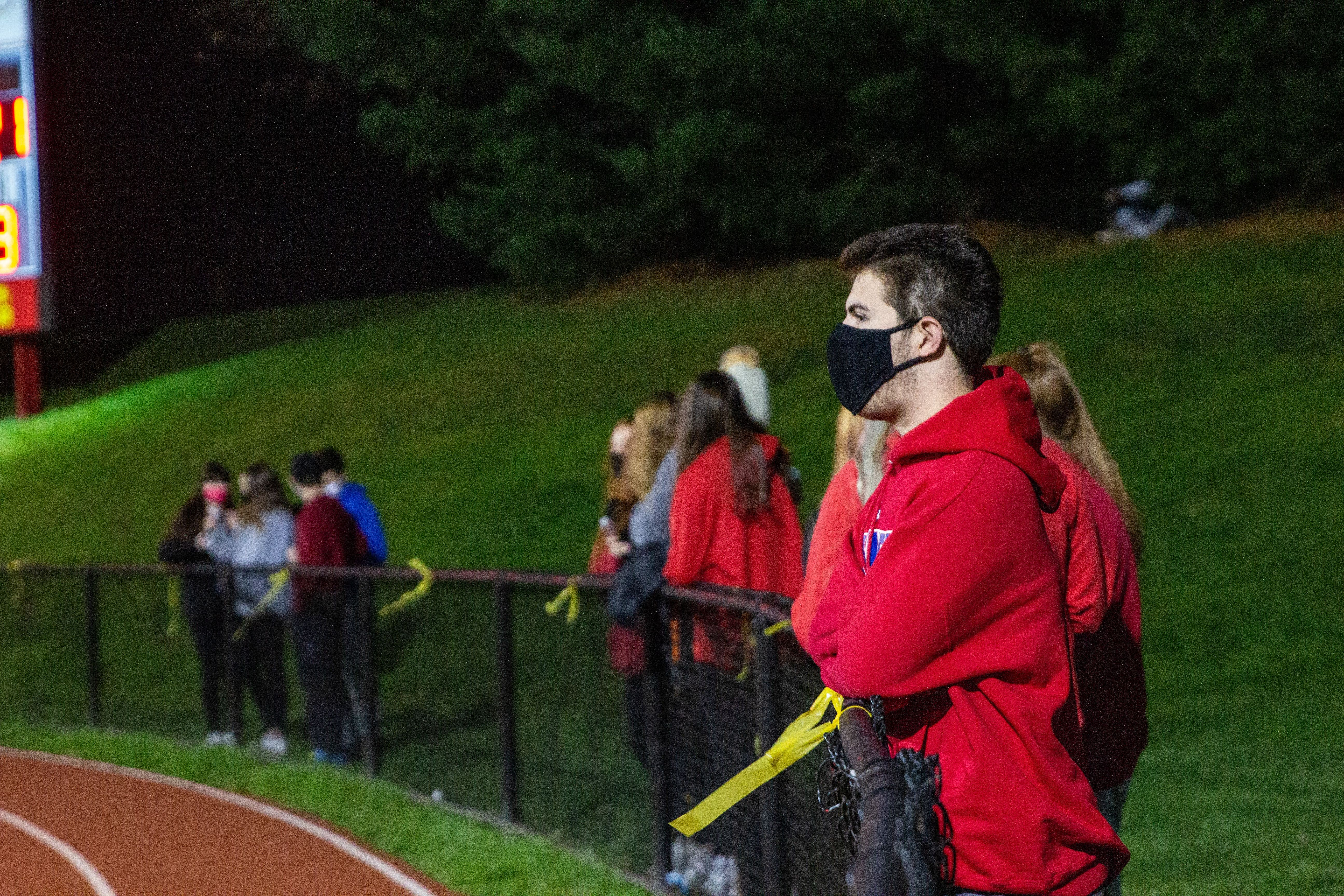 Student spectators from Penncrest High School watch the Media Bowl masked and distanced Friday.