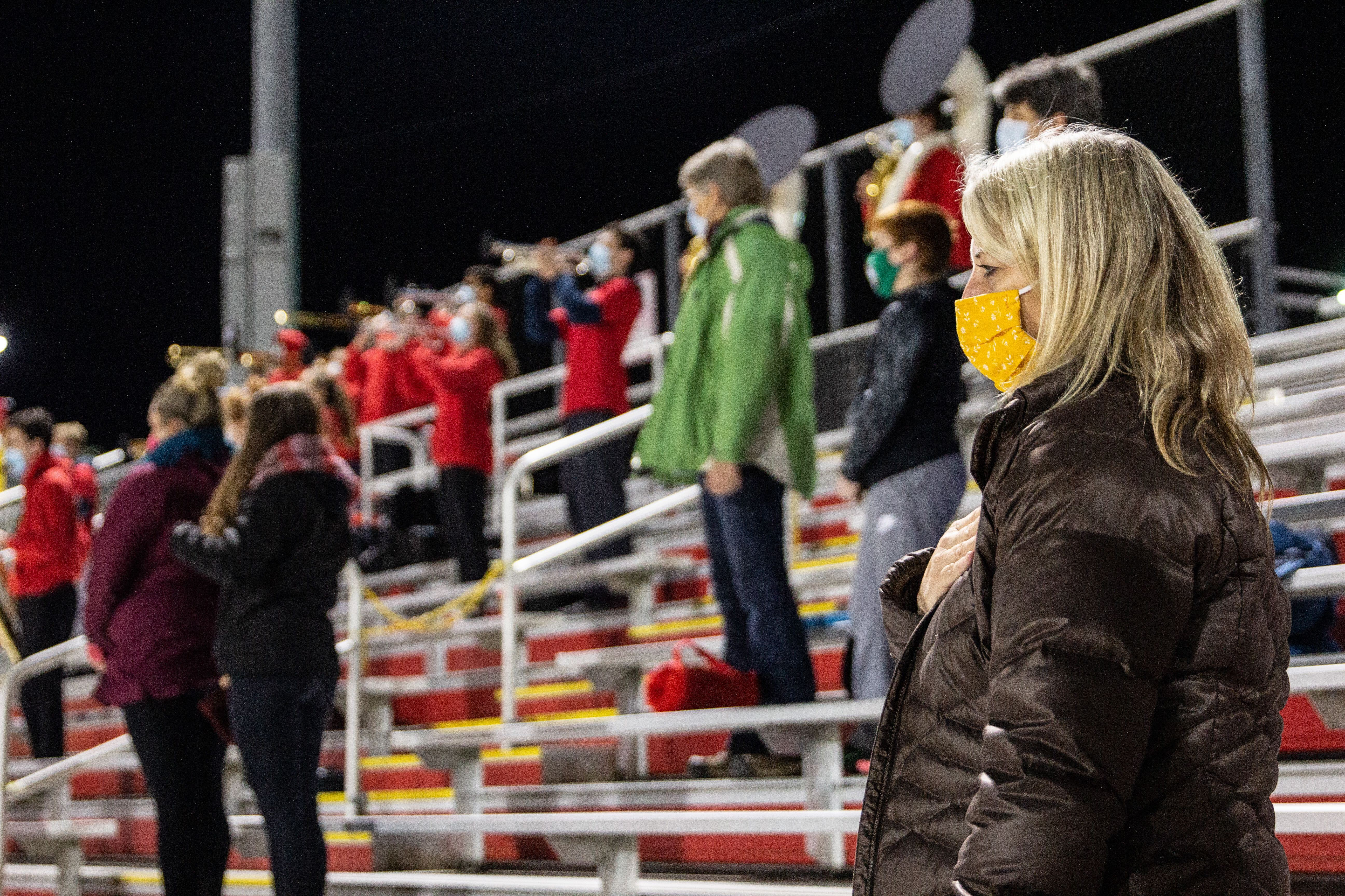 Masked and distanced parents of Penncrest High School football players stand for the national anthem before the Media Bowl.