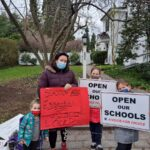 Jennifer Singer with her children, protesting Montgomery County's two-week shutdown