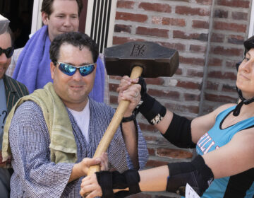 Mike 'Scoats' Scotese (Left) holds the Philly Beer Week Hammer of Glory outside Grey Lodge Pub in 2015. (Danya Henninger/Billy Penn)