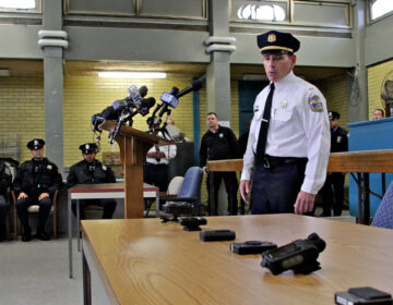 Lt. Tom McLean displays the array body camera models the police department tested when the the program began in 2014. (Emma Lee/WHYY, file)