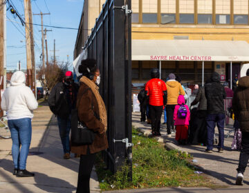 People stand in line outside Sayre Health Center for COVID testing a week before Thanksgiving in West Philadelphia. (Kimberly Paynter/WHYY)