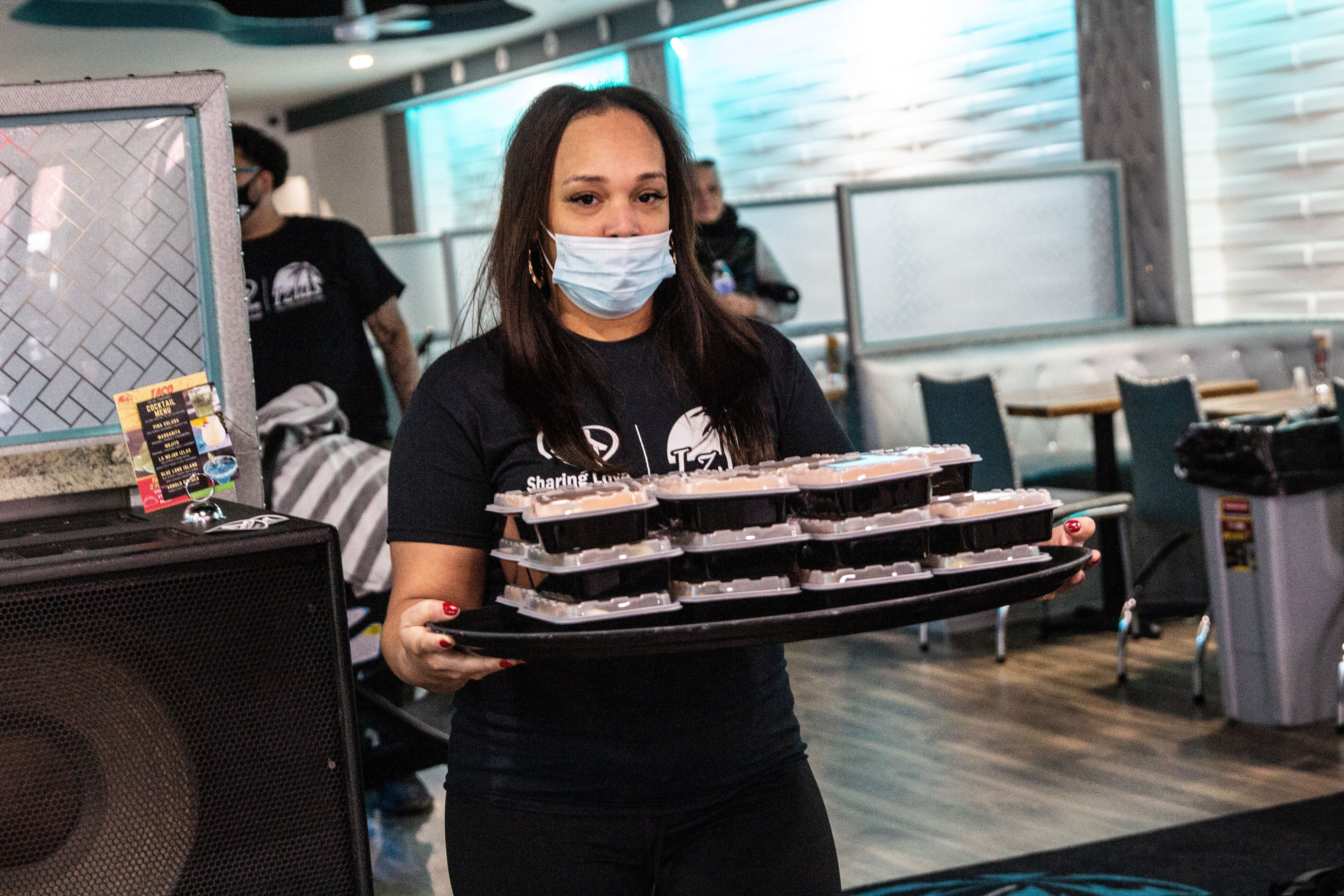 Christina Mclendon carries a plate of food during a giveaway event