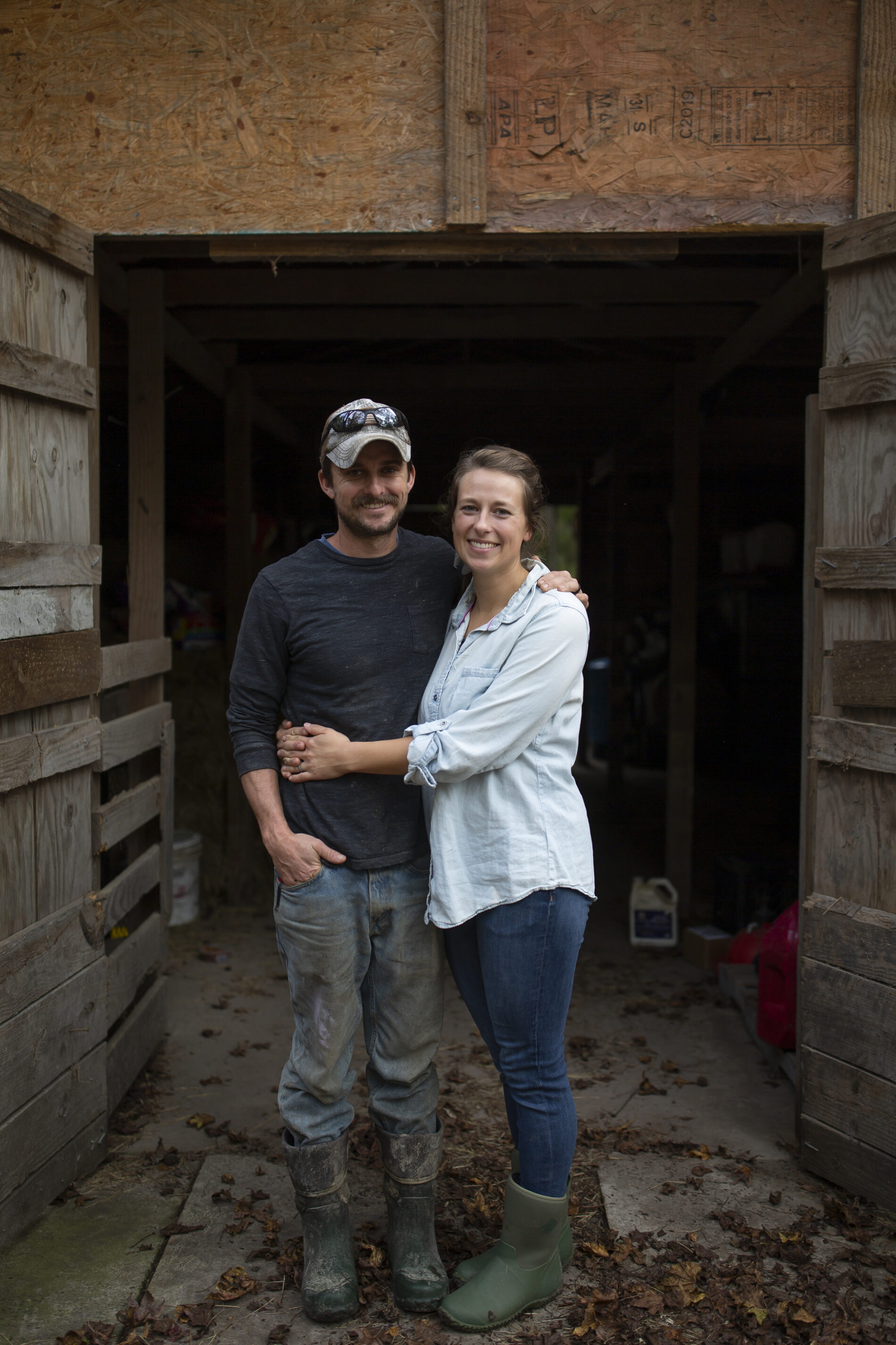 Joe Shenk, left, and Rachel Shenk, right, stand on their farm in Newport, N.C., on Nov. 15, 2020. The Shenks started their farm in 2017 with a desire to create a life that allowed them to focus on working together as a family. They now farm turkeys, chickens, and pigs. They hope to add cows in the near future as they continue to farm full-time. [Madeline Gray for NPR]