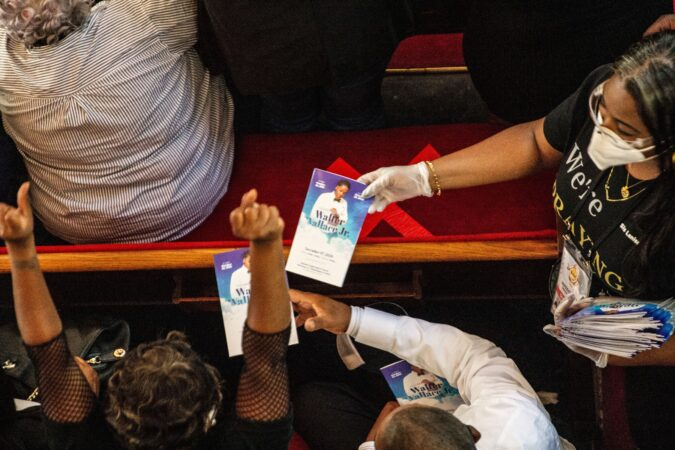 The New Temple Baptist Church staff hand out programs at Walter Wallace Jr.'s funeral service.