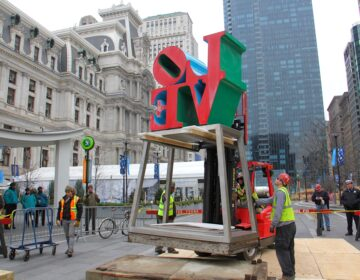 Workmen raise the LOVE statue off its pedestal in Dilworth Park in February 2017