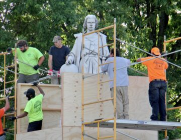 Workers box up the statue of Christopher Columbus at Marconi Plaza