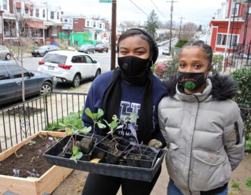 Princess Rahman (left) and Hajjah Glover finish installing a raised garden bed in Southwest Philadelphia. (Emma Lee/WHYY)