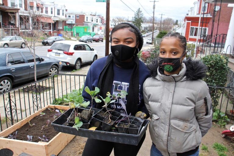 Princess Rahman (left) and Hajjah Glover finish installing a raised garden bed in Southwest Philadelphia. (Emma Lee/WHYY)