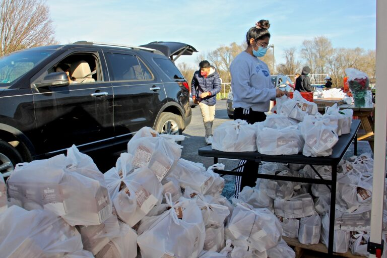 Volunteers load bags of milk for children into cars at the West Grove United Methodist Church. (Emma Lee/WHYY)