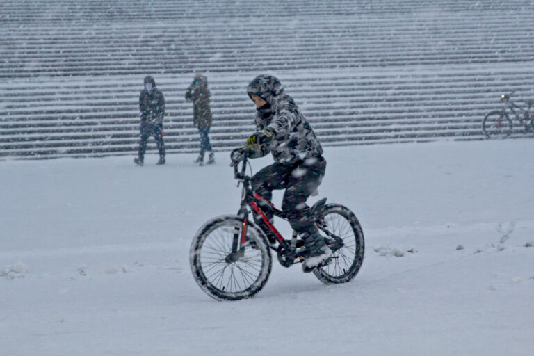 A person rides a bike during a snow storm outside the Philly Art Museum