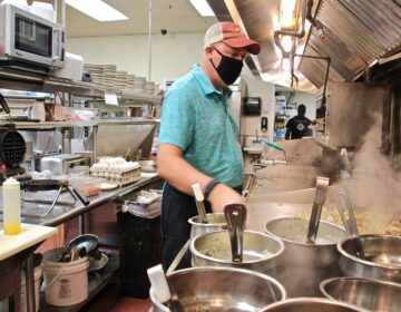 Mike Grafenstine works in the kitchen of his restaurant in Abington, Pa. (Emma Lee/WHYY)