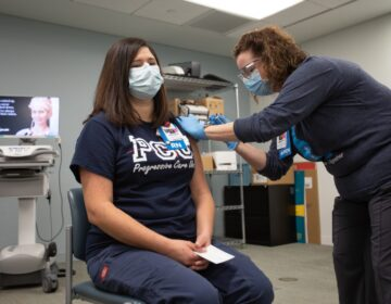 Bayhealth nurse Elisabeth Cote was vaccinated by co-worker Brittany Oakley