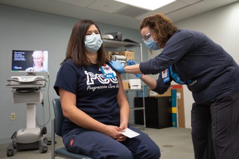 Bayhealth nurse Elisabeth Cote was vaccinated by co-worker Brittany Oakley