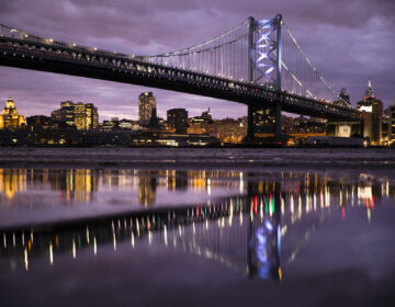 The Benjamin Franklin Bridge spanning the Delaware River between Camden N.J., foreground, and Philadelphia is reflected the mud revealed amid low and high tide, Thursday, Dec. 5, 2019. (AP Photo/Matt Rourke)