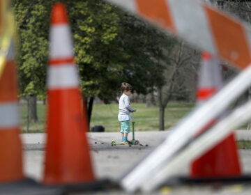In this March 31, 2020 file photo, a child rides a scooter past barricades at an entrance to Tower Grove Park in St. Louis. (AP Photo/Jeff Roberson)