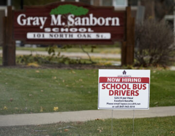 A hiring sign shows outside of Gray M. Sanborn Elementary School in Palatine, Ill., Thursday, Nov. 5, 2020. Illinois reports biggest spike in unemployment claims of all states. On Wednesday, Dec. 23, the number of Americans seeking unemployment benefits fell by 89,000 last week to a still-elevated 803,000, evidence that the job market remains under stress nine months after the coronavirus outbreak sent the U.S. economy into recession and caused millions of layoffs.  (AP Photo/Nam Y. Huh)