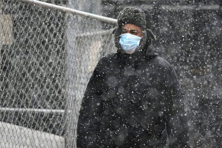 A man wearing a mask walks through a mid-afternoon snow squall in downtown Pittsburgh on Tuesday, Nov. 17, 2020. (AP Photo/Gene J. Puskar)