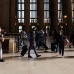 Travelers wait in line to board a train at the 30th Street Station ahead of the Thanksgiving holiday, Friday, Nov. 20, 2020, in Philadelphia. (AP Photo/Matt Slocum)