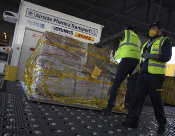 Cargo workers move a palette of cool boxes and other items into a pharma transport container during a demonstration on the handling and logistics of vaccines and medicines at the DHL cargo warehouse in Steenokkerzeel, Belgium, Tuesday, Dec. 1, 2020. (AP Photo/Virginia Mayo)