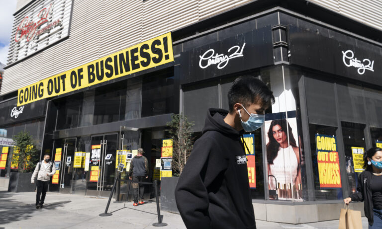 In this Wednesday, Sept. 30, 2020, file photo, a man wearing a mask amid the coronavirus pandemic walks by a Century 21 department store, in the Brooklyn borough of New York. (AP Photo/Mark Lennihan)