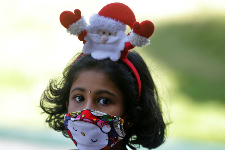 A Sri Lankan Catholic girl wears a hair band with a Santa figure arrives at a church to attend the Christmas Day holly mass in Colombo, Sri Lanka, Friday, Dec. 25, 2020. (AP Photo/Eranga Jayawardena)