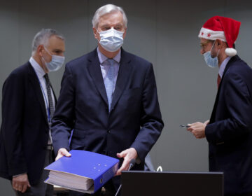 A colleague wears a Christmas hat as European Union chief negotiator Michel Barnier, center, carries a binder of the Brexit trade deal during a special meeting of Coreper, at the European Council building in Brussels, Friday, Dec. 25, 2020. (Olivier Hoslet, Pool via AP)