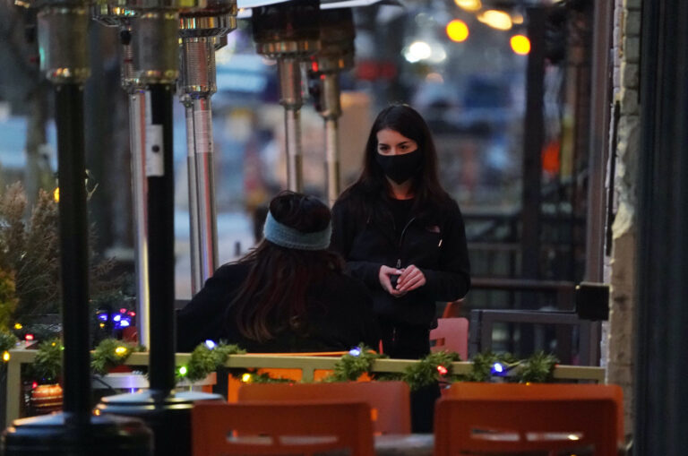 A waitperson wears a face mask while tending to a patron sitting in the outdoor patio of a sushi restaurant late Monday, Dec. 28, 2020, in downtown Denver. (AP Photo/David Zalubowski)